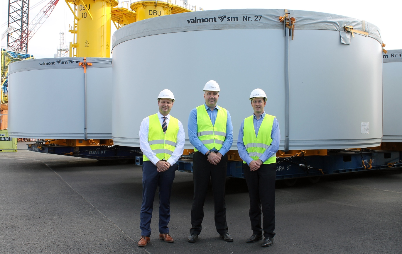 (f.l.t.r.) Roland Schneider, Head of Business Development at Cuxport, Anders Engelhardt, Global Project Manager at FREJA Transport & Logistics A/S, and Marcus Braue, Branch Manager of  DFDS Germany ApS & Co. KG in Cuxhaven, at berth no. 4 in front of the wind turbine components loaded onto Mafi trailers. Picture source: HWG.